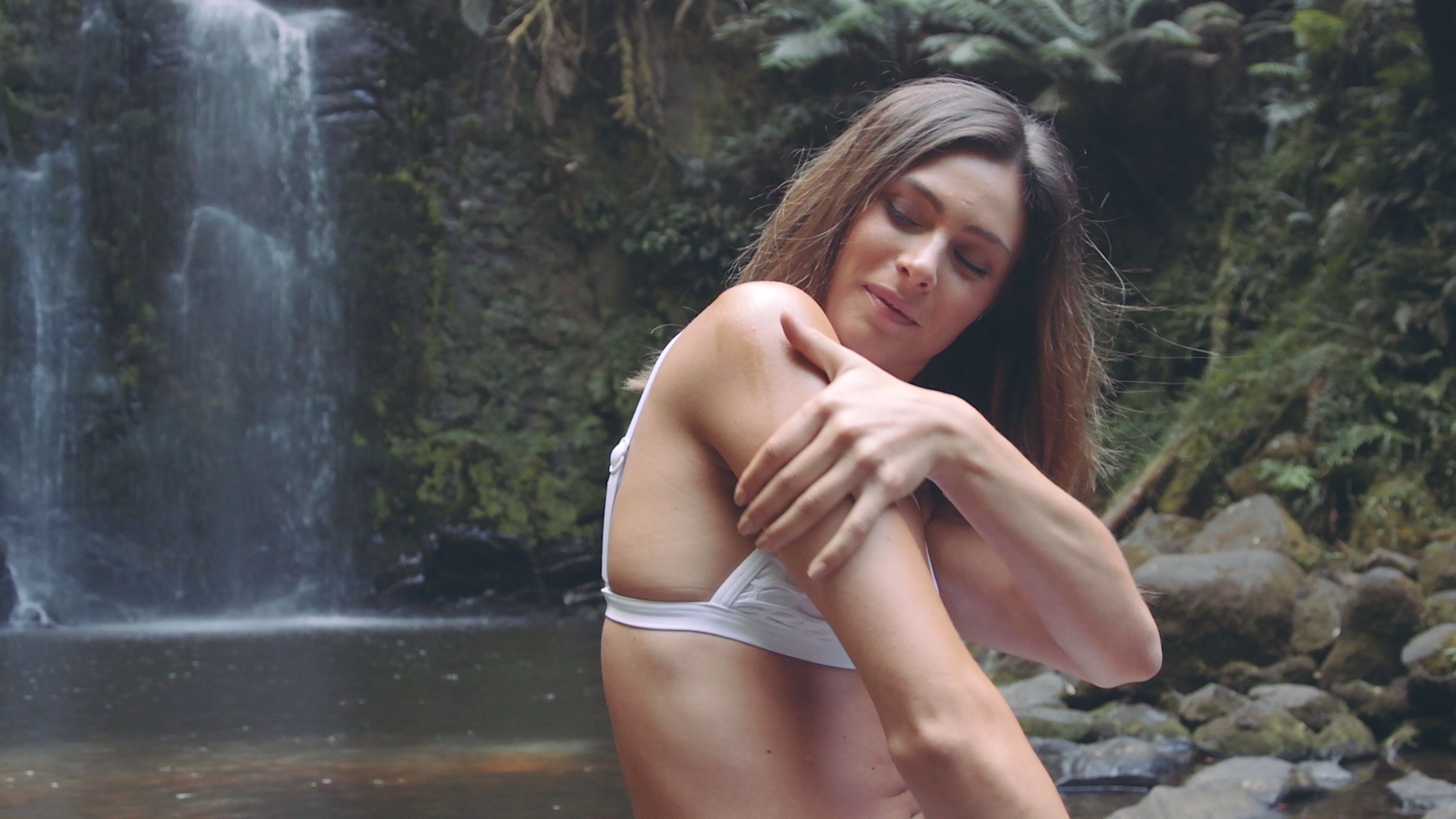 Woman applying natural lotion in front of waterfalll
